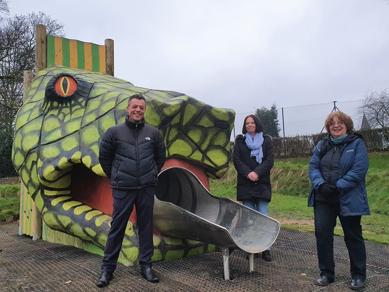 Councillor Bob Johnson, Councillor Mary Lea and Christine Welburn (FoHP) stand next to the giant snake head slide at Hillsborough playground